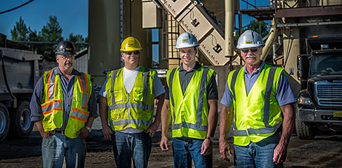Four construction workers wearing hard hats and safety vests.